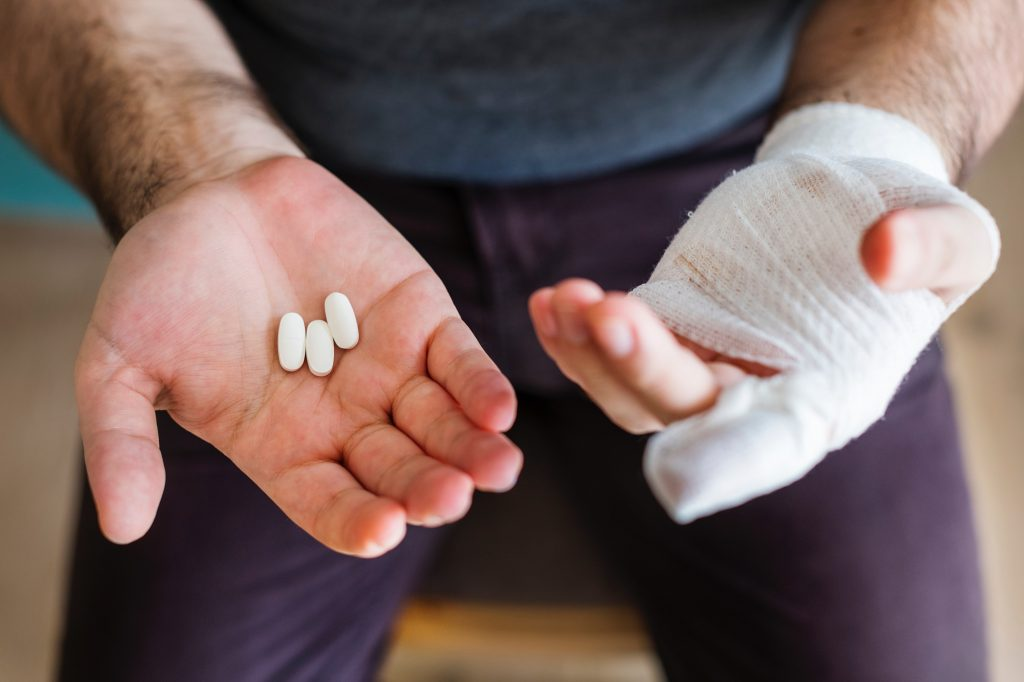 Picture of a man with bandaged hand and pain medication.