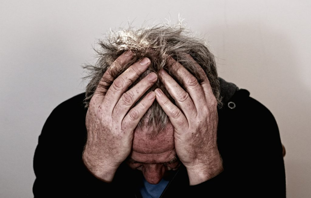 Picture of a man with a brain injury holding his head in his hands.